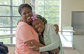Two black women hugging and smiling at camera