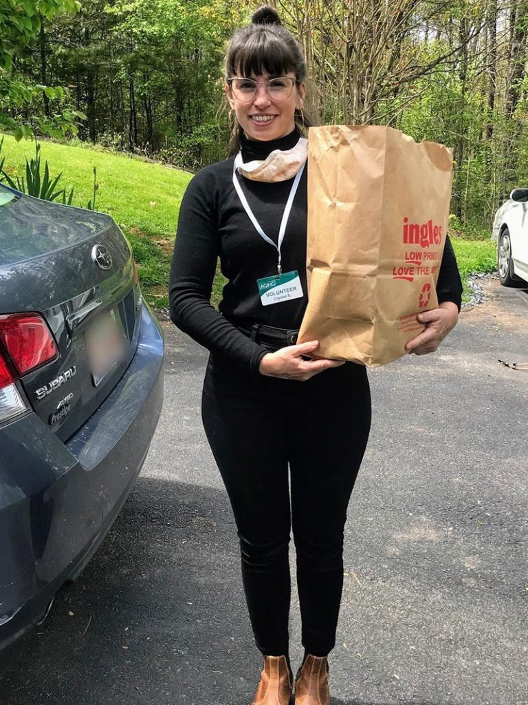 smiling girl holding bag of donated food